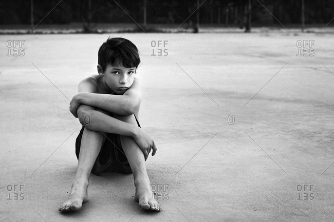 Boy sitting alone on ground