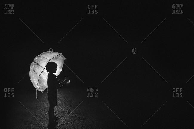 Child standing under an umbrella at night