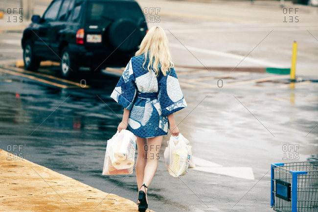 Woman in quilted kimono carrying groceries