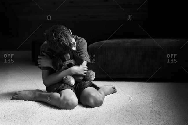 Boy hugging desperately his plush puppy
