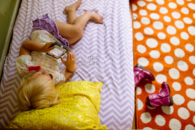 Overhead of young girl on bed playing with smartphone