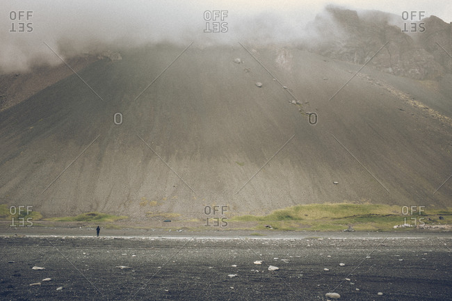 Person standing at foot of hill under fog, Iceland