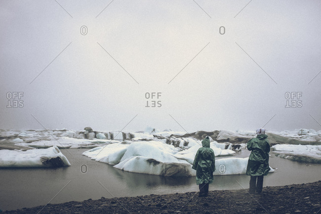 Couple in cagoules looking at ice in water, Iceland