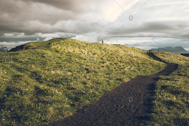 Solitary man standing on grassy hill, Iceland