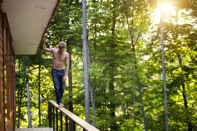 Man walking along porch banister
