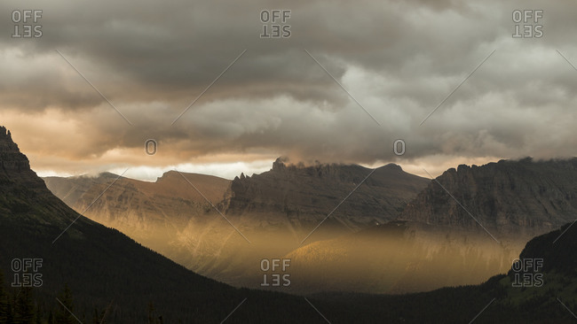 Light streams through a mountain range during sunrise