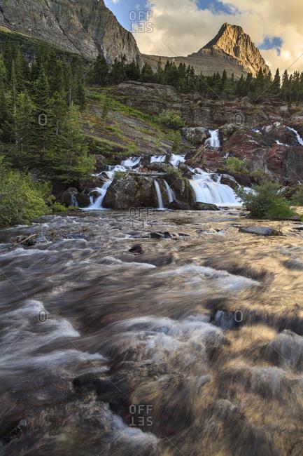 a river flows near a waterfall through a mountainous valley