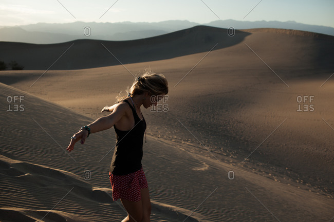 Young woman with arms outstretched descends sand dune, Death Valley, California