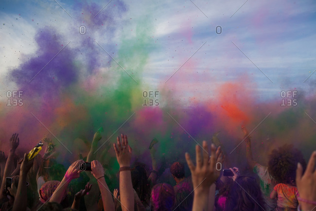 Crowd throws colored powder into the air at the Festival of Colors, based on Holi, Brooklyn, New York