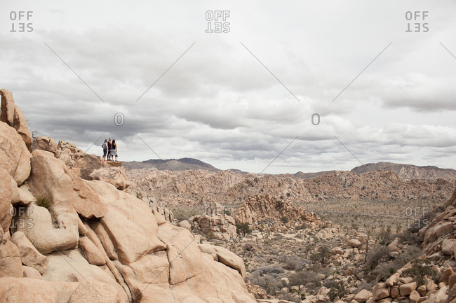 Three tourists looking over the desert scrublands, Joshua Tree National Park, California