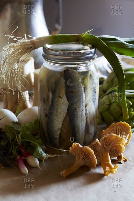 Pickled sardines and raw vegetables on a table