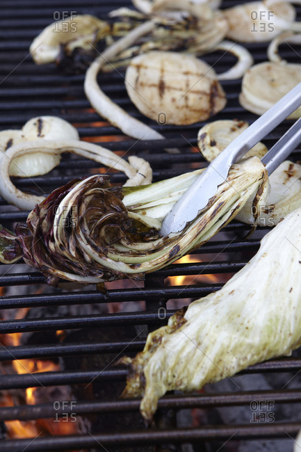 Close up of onions, mushrooms and endives on a grill