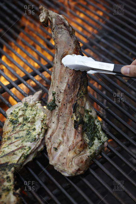 Holding grilled lamb chop with tongs