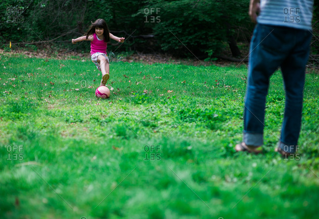 Young girl kicking soccer ball