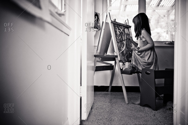 A young girl painting at an easel