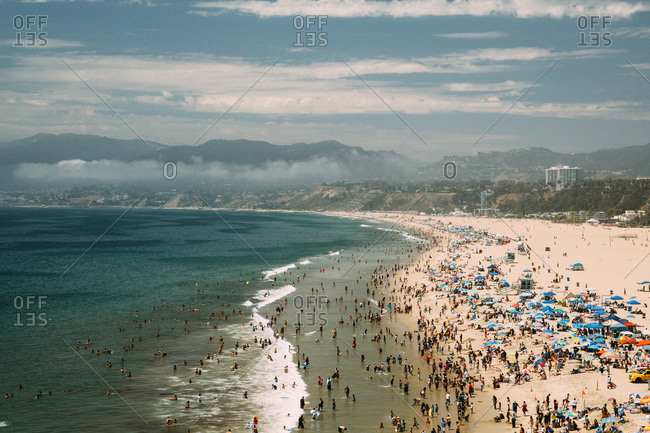 Aerial view of crowded beach with sunshades