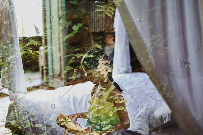 Girl standing in a room with plants reflecting in a window glass