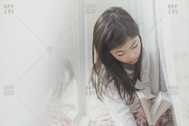 Girl reading a book by the window