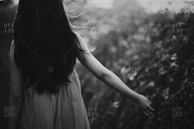 Back view of girl walking in a meadow