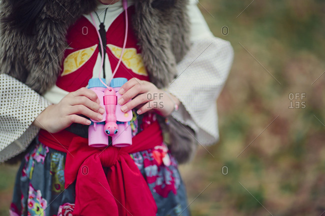 Close up of a girl holding toy binoculars