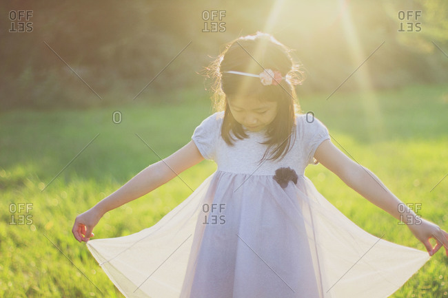 Girl standing in the sunshine in a field