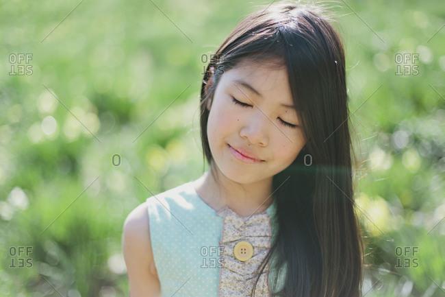 Portrait of girl enjoying the sunshine in a meadow