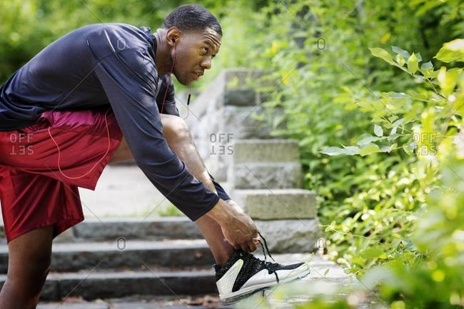 Side view of man tying shoes before jog
