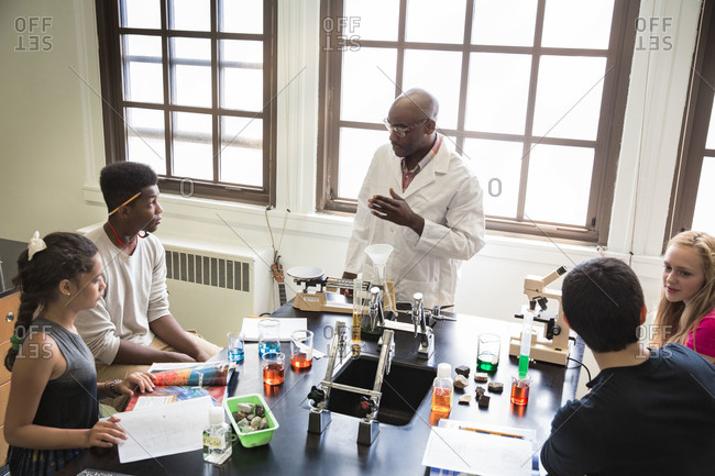 Man teaching chemistry to his students in a school