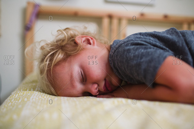 Blonde boy napping in bed