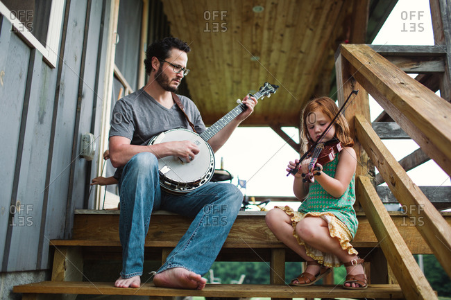 Father and daughter playing music on porch
