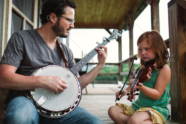 Dad and his daughter practicing together on porch