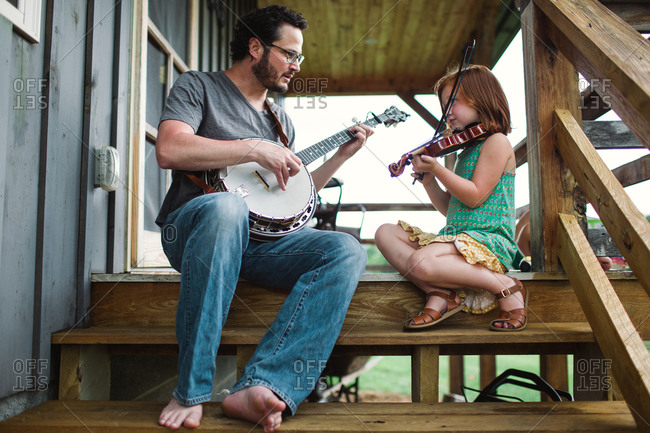 Man and girl playing music on stair of a porch