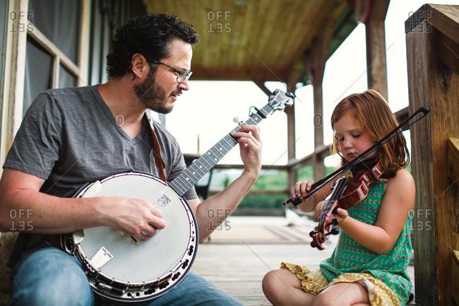 Man playing a banjo accompanied by a girl playing violin