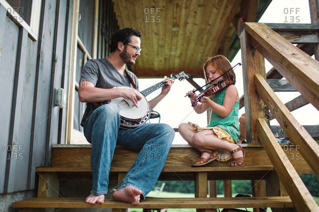 Low angle view of father and his daughter playing music on porch