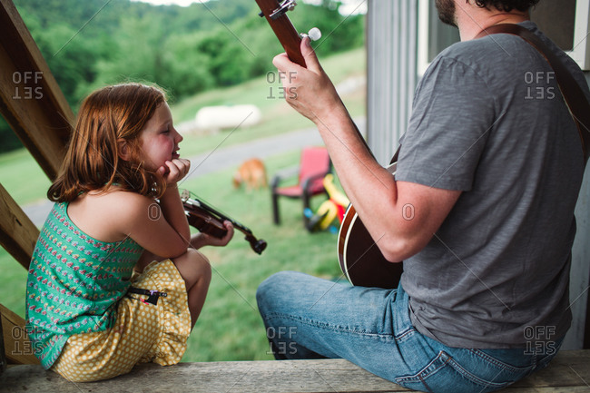 Father playing a banjo while his daughter listening