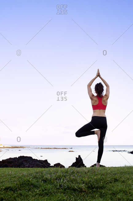 Rear view of woman doing tree yoga pose