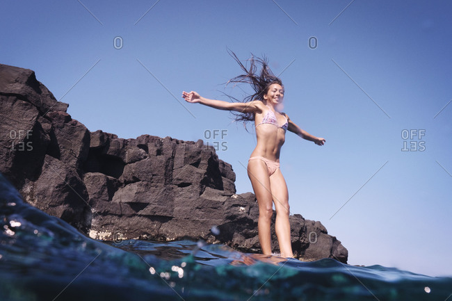 Jumping off rocks with outstretched arms