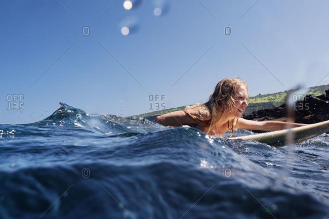 Woman paddling on surfboard, Hawaii, USA