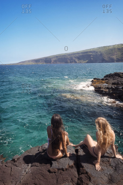 Rear view of two women watching the Pacific Ocean, Hawaii, USA