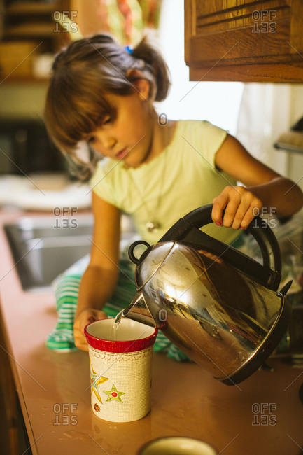 Girl on countertop pouring hot water into a mug