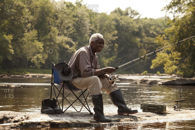 Smiling man fishing on river shore