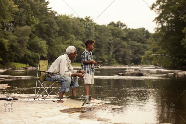 Grandfather and grandson fishing in river