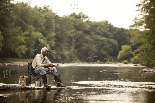 Relaxed man fishing from river shore