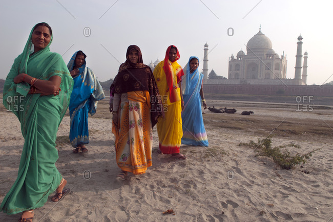 Agra, India - January 9, 2007: Women wearing colorful saris walking past the Taj Mahal on the banks of the nearly dry Yamuna River