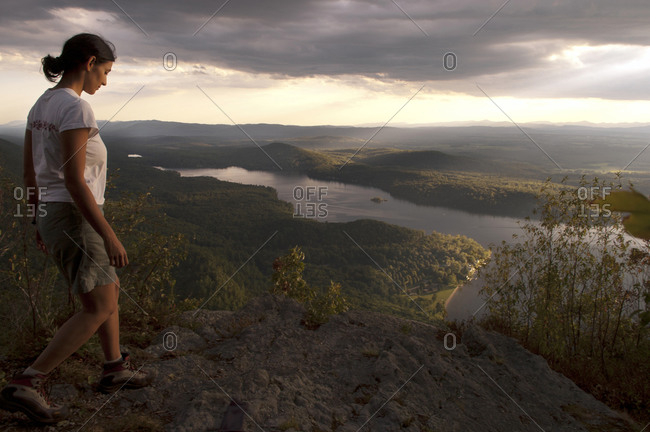 Green Mountain National Forest, Vermont, USA - September 3, 2005: A woman hiking at sunset at Rattlesnake Cliffs in the Moosalamoo National Recreation Area in Vermont with Lake Dunmore in the background