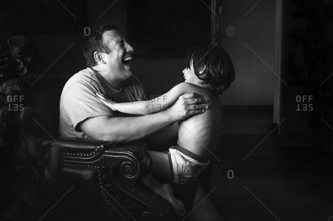 Laughing father holding his son