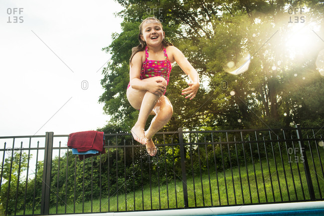 Low angle view of young girl jumping into pool