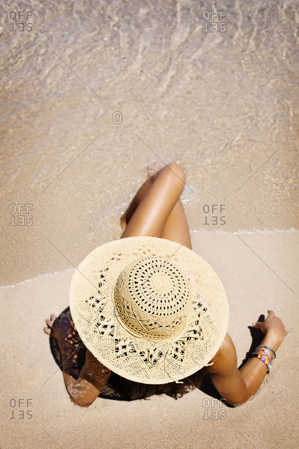 High angle view of woman sun-bathing on beach