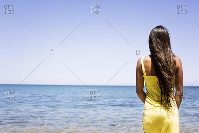 Woman standing on beach in yellow summer dress