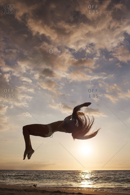 Woman jumping on a beach at sunset